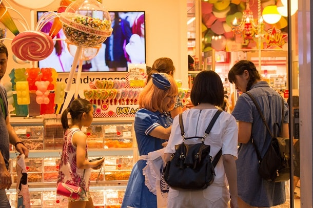 Maid at entrance to candy store